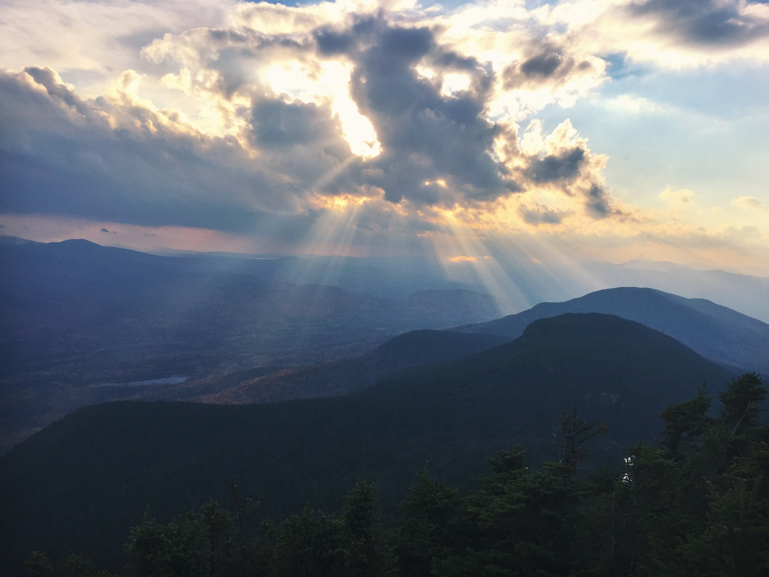 The evening sun hides behind the clouds, view west from the South Horn.