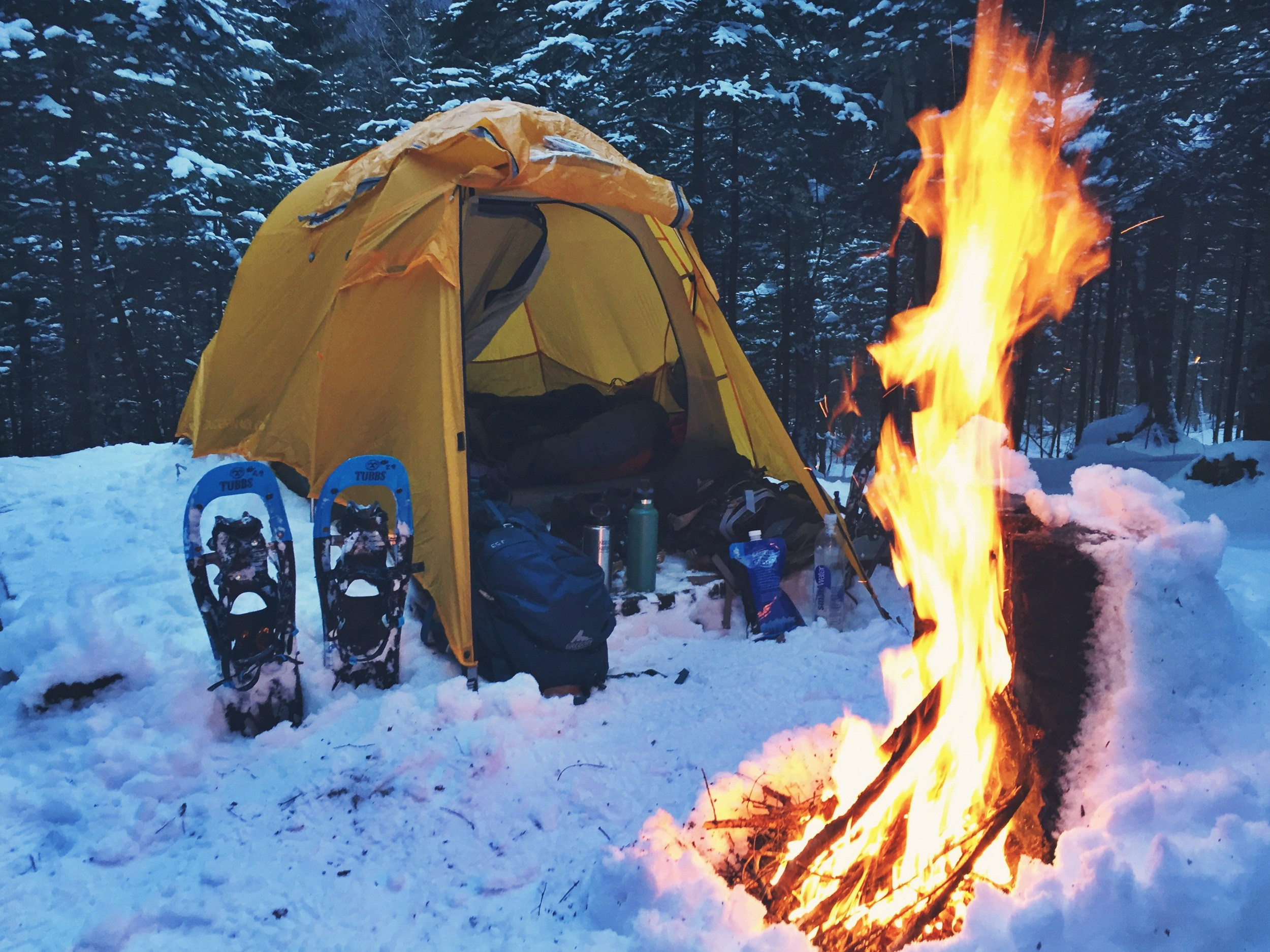 While Moose warms up her sleeping bag, Teton generates a little warmth with a small kindling fire.