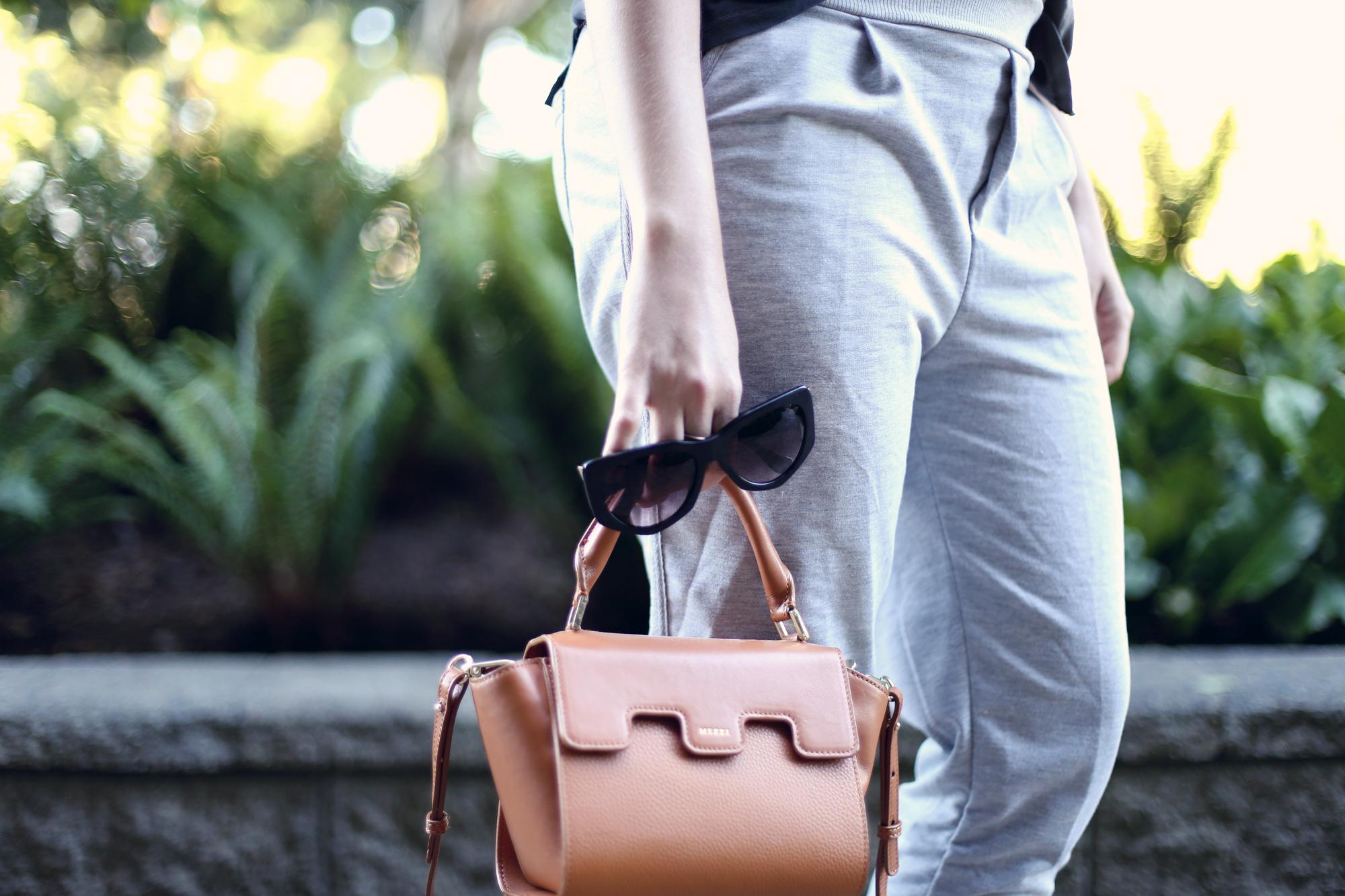 Minimalist accessories: a tan leather bag and black sunglasses.
