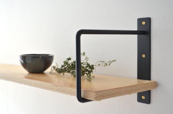 The best Etsy decor: black shelf brackets with gold screws and a pine shelf.