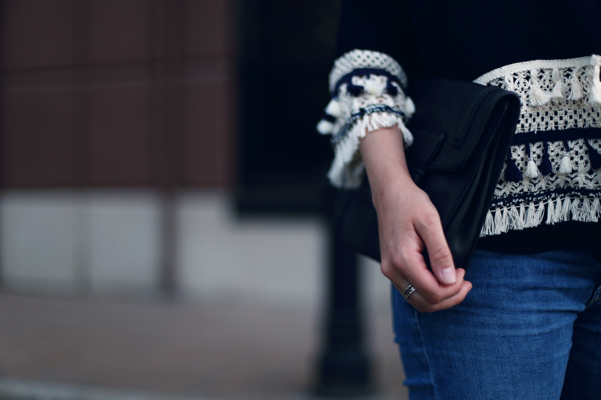Minimalist outfit details: tassels, oversized black clutch, and skinny jeans. #ootd