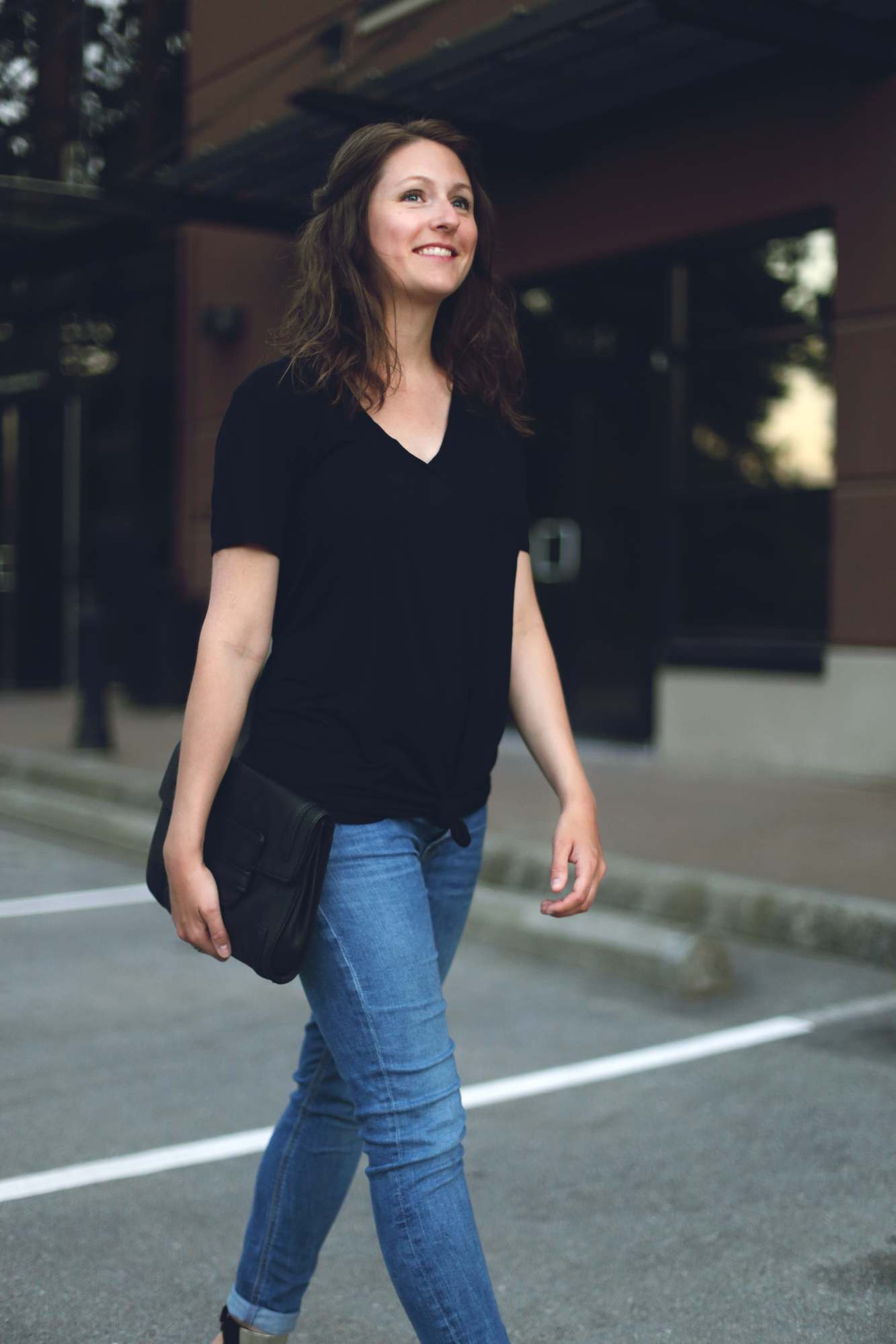 Minimalist street style chic outfit: black t-shirt, skinny jeans, and an oversized clutch.