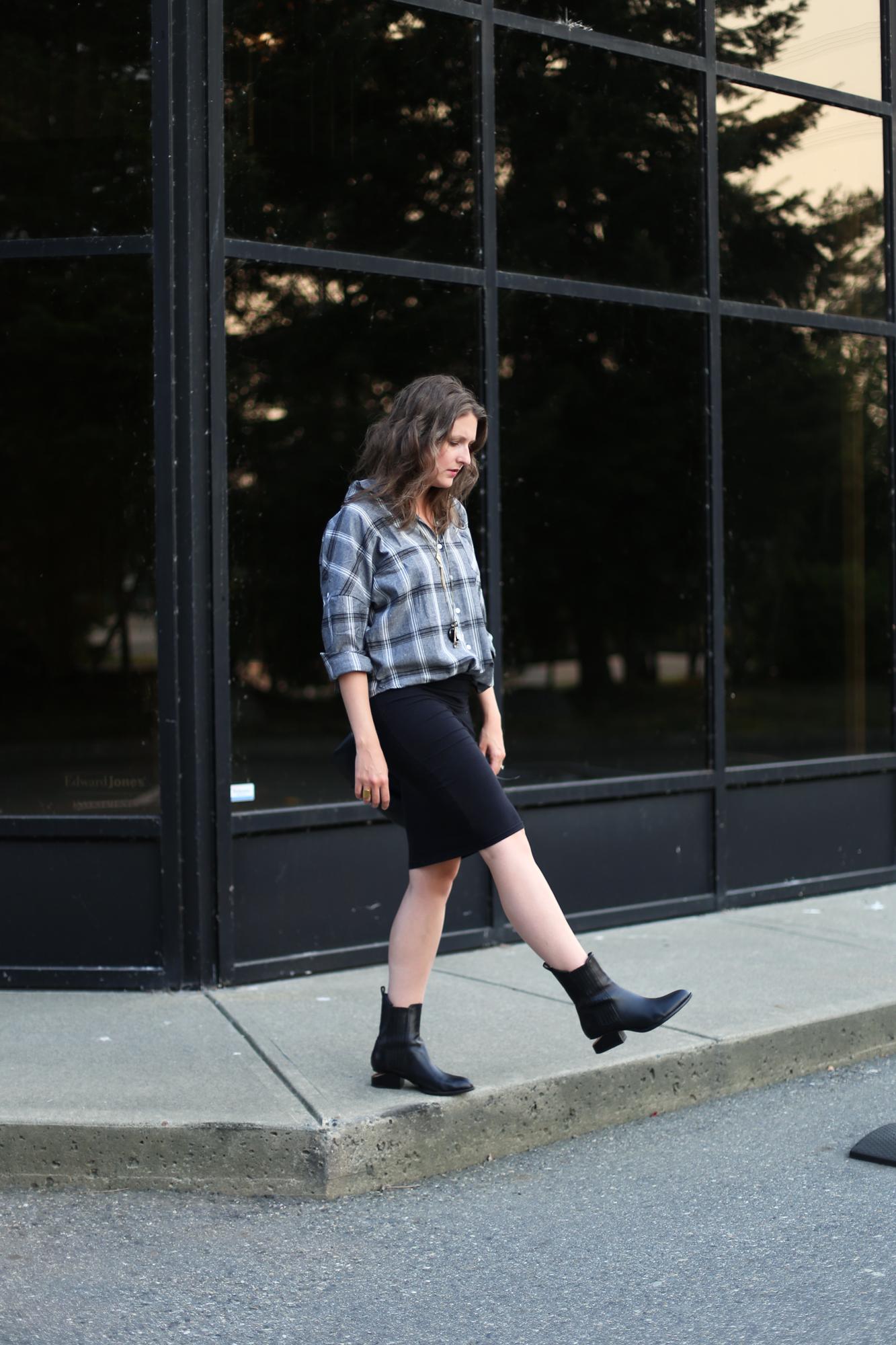 minimalist outfit ideas: black bag, black skirt, alexander wang boots, and a plaid shirt.