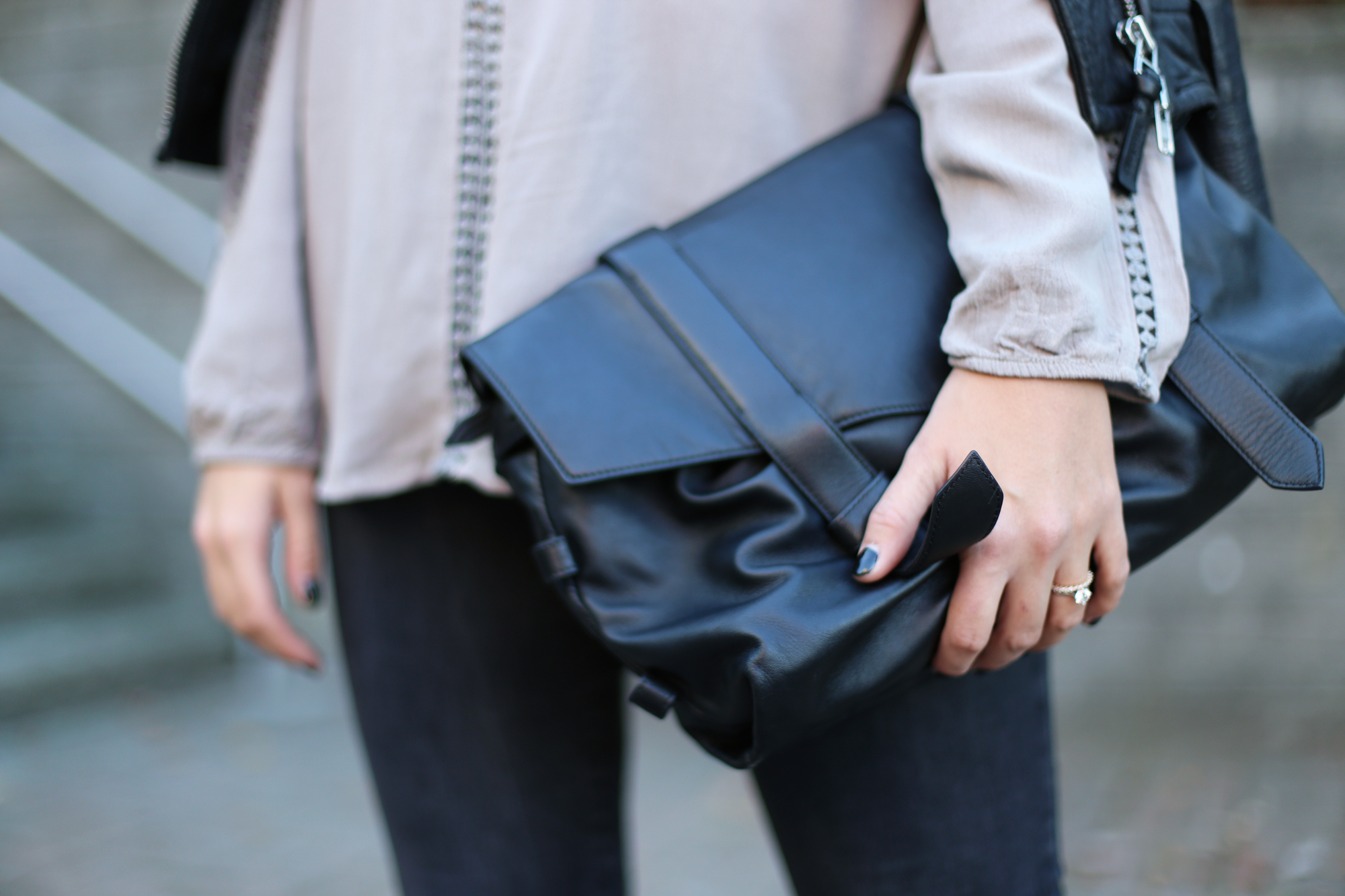 Minimalist street style: black leather purse and black nails.
