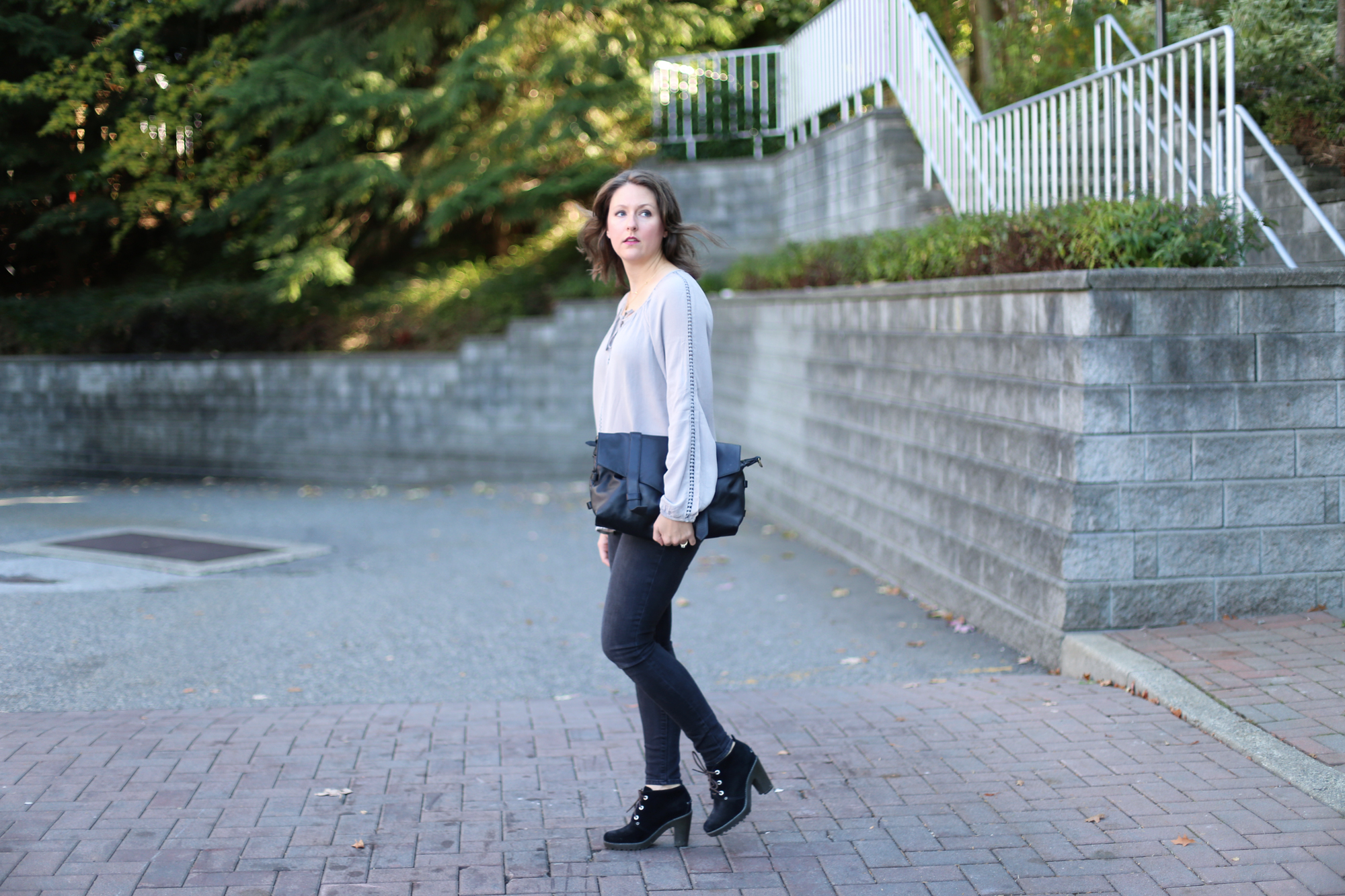 Super chic, minimalist street style outfit. Flowy blouse, black leather bag, black nails, and black skinny jeans.