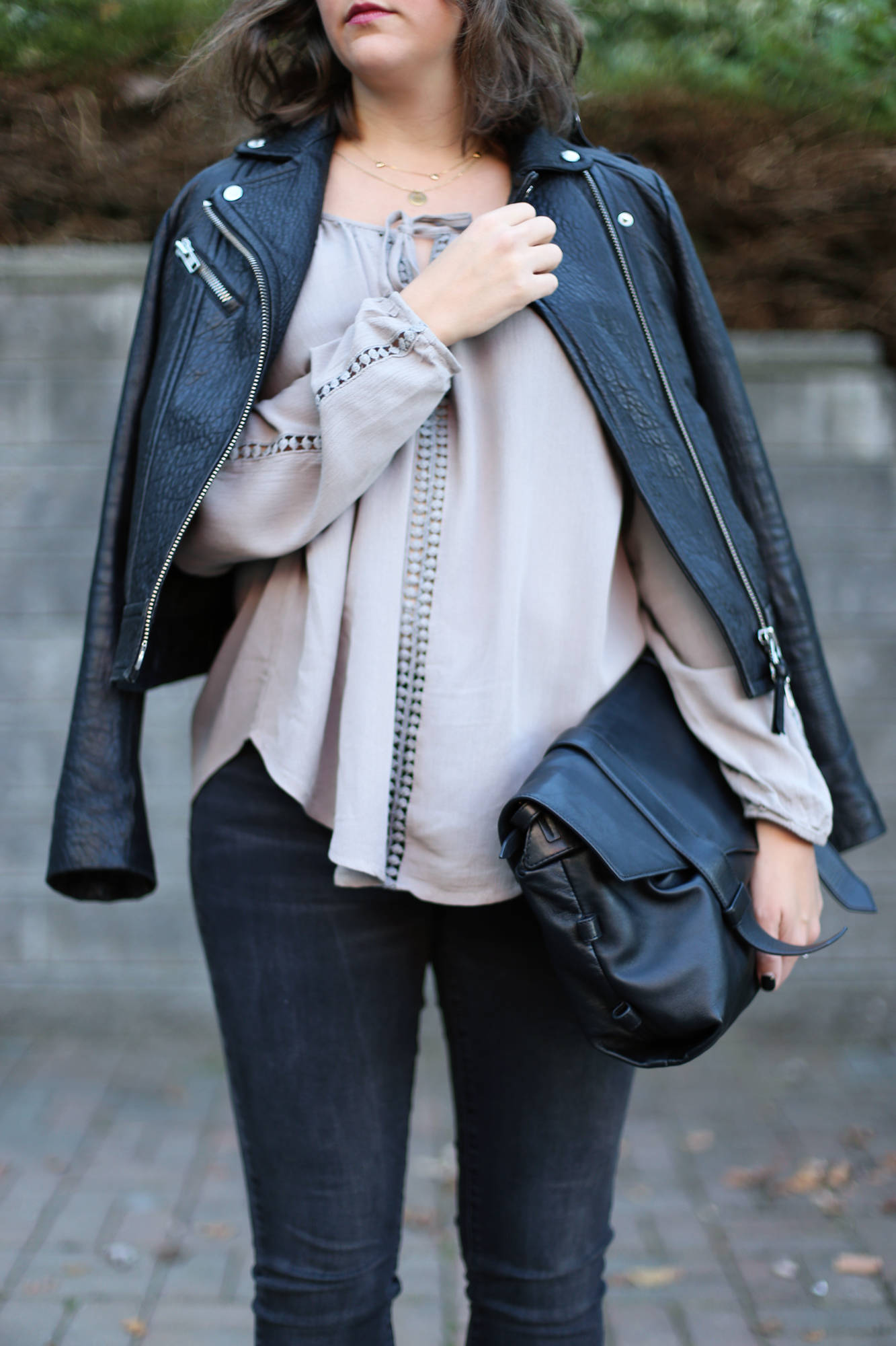 Minimalist street style: black leather moto jacket, oversized blouse, black nails, and an oversized bag.