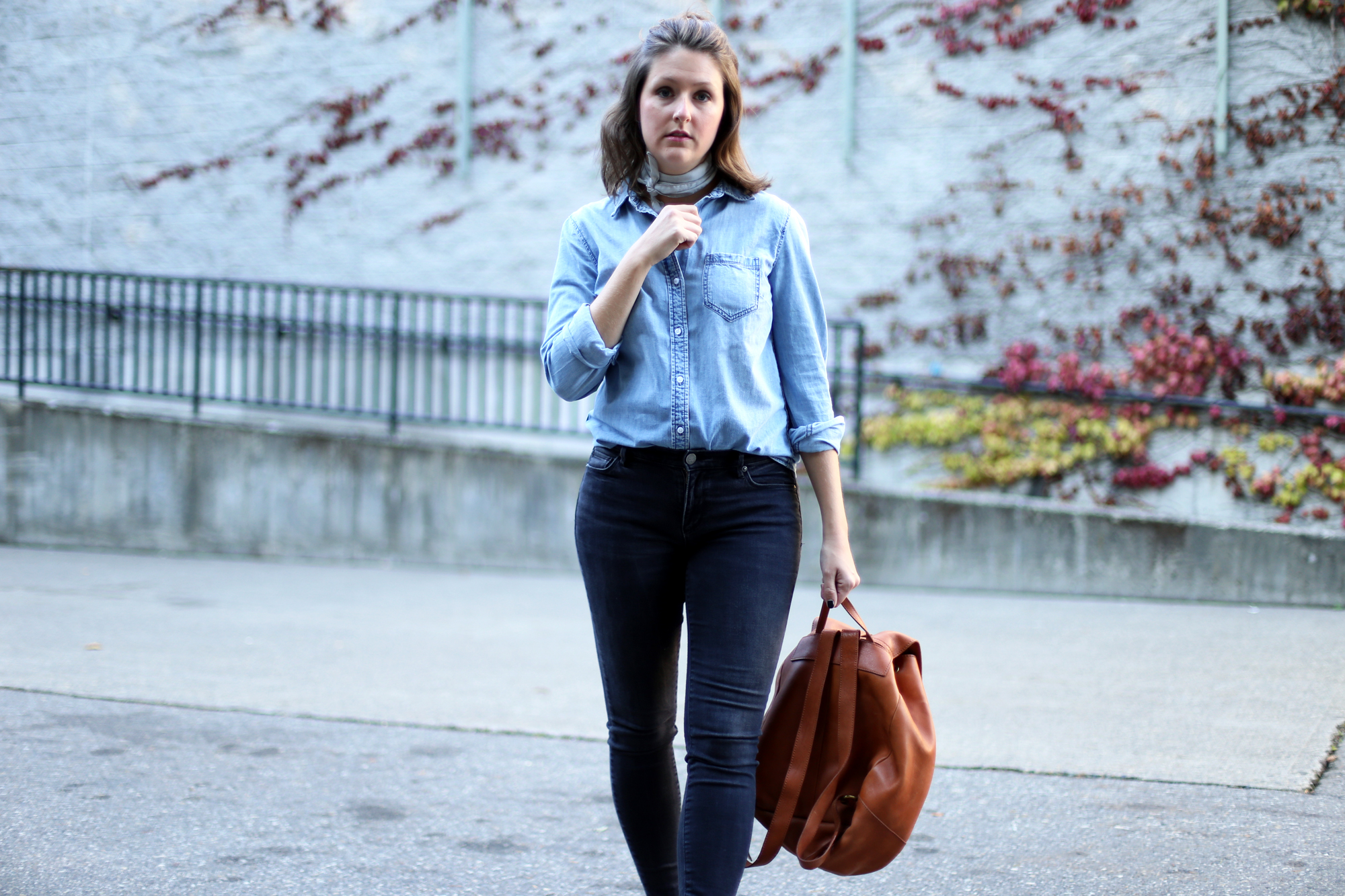 Fall essentials: leather backpack, denim button up shirt, black skinny jeans, minimalist jewellery, and a neck scarf.