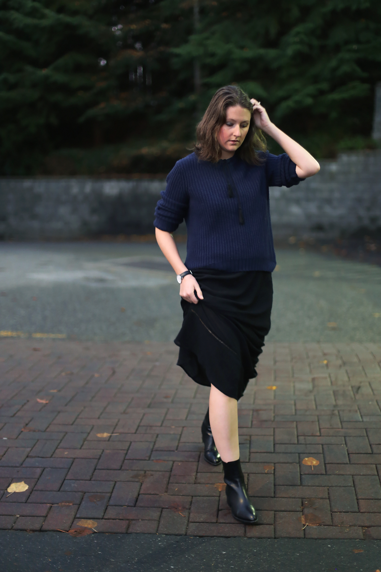 Minimalist street style: oversized sweater, black maxi dress, Alexander Wang boots, and a Daniel Wellington watch.