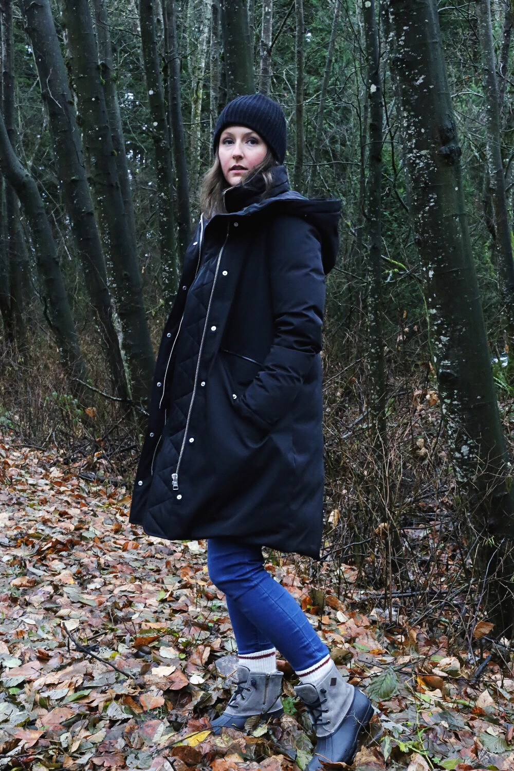 Winter street style: oversized black parka, waterproof rain boots, and a black toque.