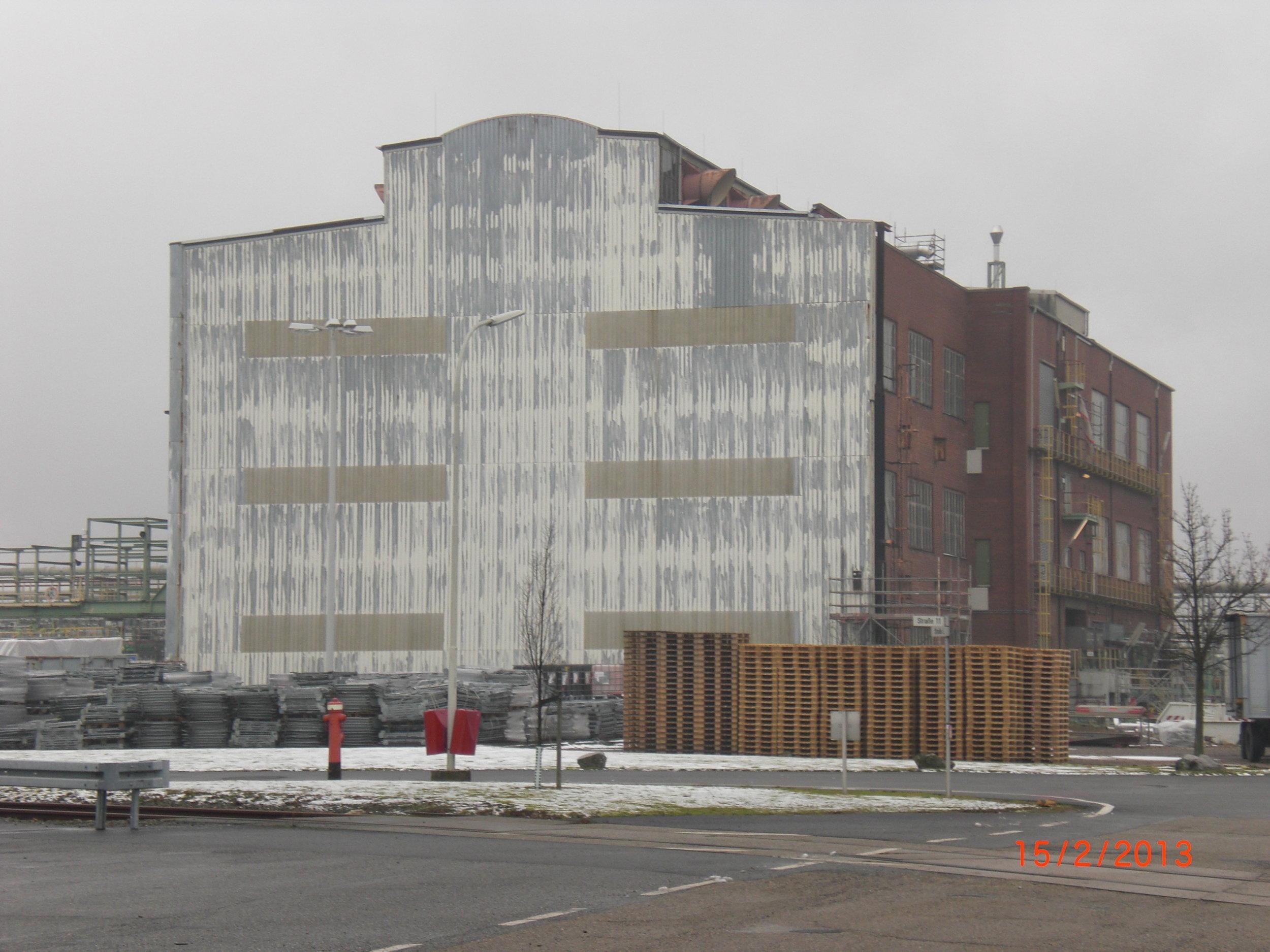 Ein altes Werksgebäude ist stark verwittert. Verschiedene Materialien der Fassade zeigen starke Schäden.