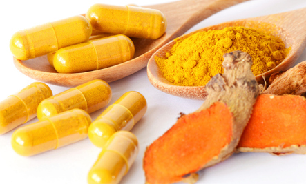 Curcumin capsules and the Tumeric root they are derived from