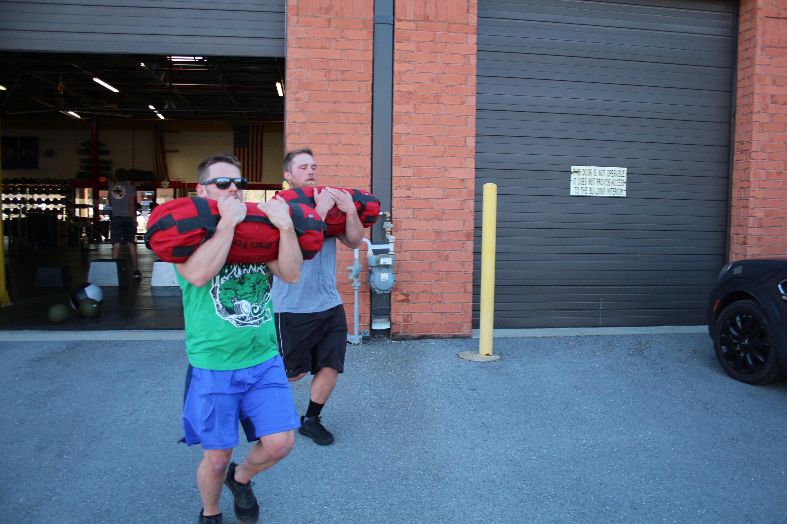 Dan and Logan Zercher carrying 75lb sandbags.