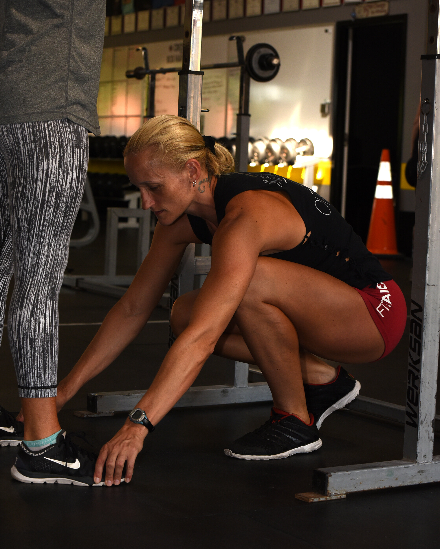 Coach Amanda adjusting an athletes feet during the Back Squat.