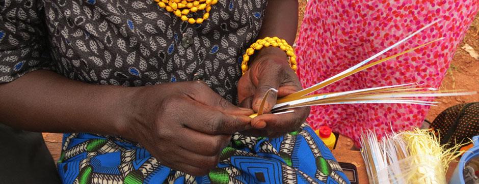 Artisan preparing paper to create beads for 22 Stars in Uganda