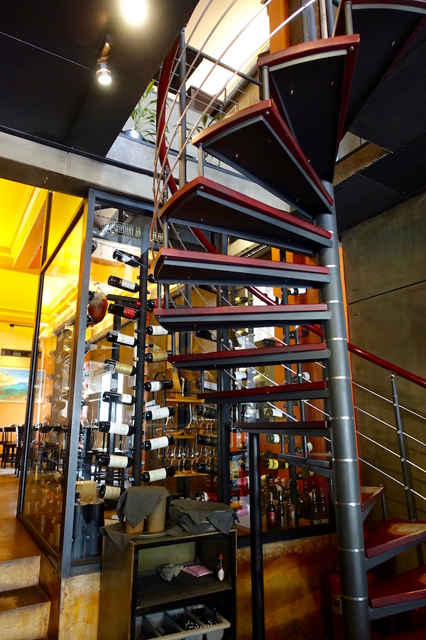 A floor to ceiling climate controlled wine cabinet sits behind the metal and wood spiral staircase. I've got to get one of those