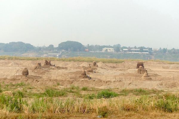 Giant sand sculptures under construction by the Mekong River