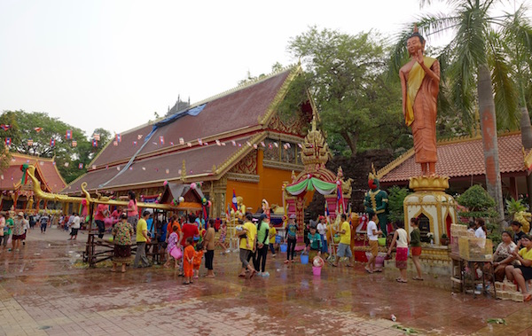 From washing the giant gold naga to posing for a photo or freeing a bird, it's a riot of colour and festival spirit at the temple in Pi Mai