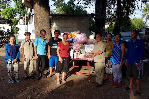 Handing over the donations and supplies to our neighbours with the head of the compound.