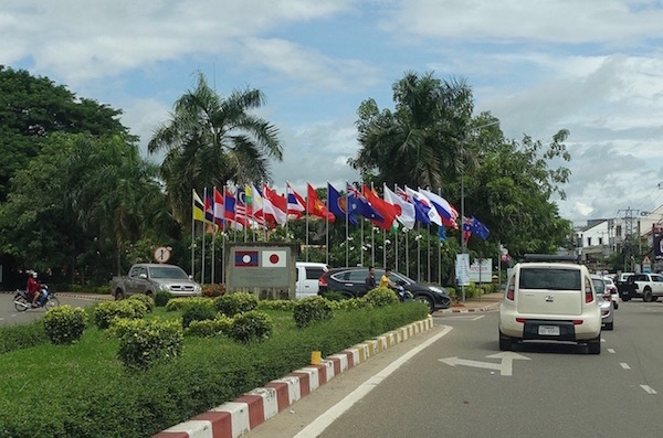 Flags fly along Thadeua, the main road into town, ASEAN Fever | Eat Drink Laos http://eatdrinklaos.com/blog/asean-fever