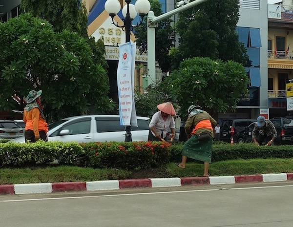 Women trim the hedges of the median strip down Lane Xang, one of the most important roads in Vientiane, ASEAN Fever | Eat Drink Laos http://eatdrinklaos.com/blog/asean-fever