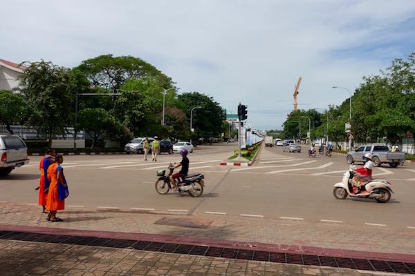 A pair of monks wait to cross the road in between motorcades, ASEAN Fever | Eat Drink Laos http://eatdrinklaos.com/blog/asean-fever