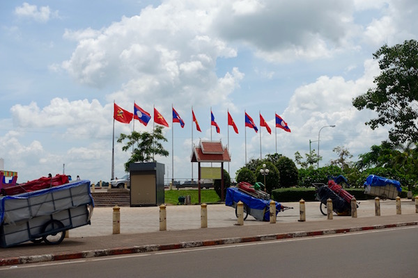 The Lao and Communist flags fly on the river road, above packed up market stalls, ASEAN Fever | Eat Drink Laos http://eatdrinklaos.com/blog/asean-fever