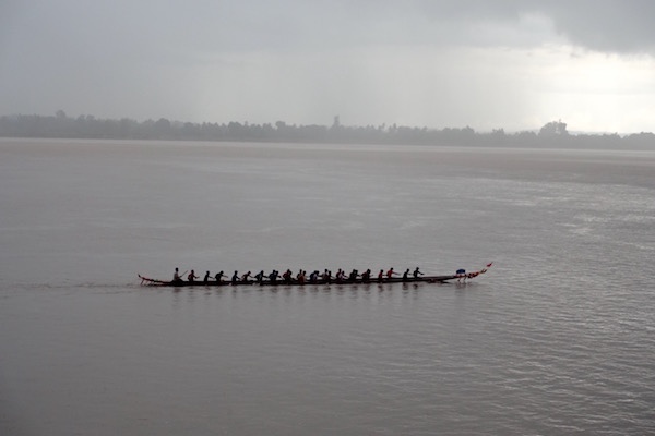 Champasak province in southern Laos in October - cool, rainy and just beautiful. It's also Boat Racing Festival time - here the wooden low boats practice for the big race as storm cloud gather over the Mekong river | Eat Drink Laos http://eatdrinklaos.com/blog/southern-laos-champasak-boat-racing
