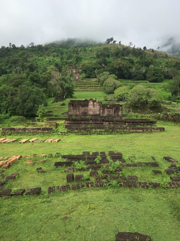 Mist shrouds the mountain but the heavy 1,000 year old carved stone structures of Wat Phu remain steadfast and vigilant. Wat Phu, a Khmer Hindu temple ruin, in Champasak, Laos | Eat Drink Laos http://eatdrinklaos.com/blog/southern-laos-wat-phu