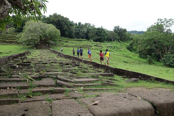 Local Lao kids run up the well worn, heavy stone steps of the 1,000 year old Wat Phu, a Khmer Hindu temple ruin, in Champasak, Laos | Eat Drink Laos http://eatdrinklaos.com/blog/southern-laos-wat-phu