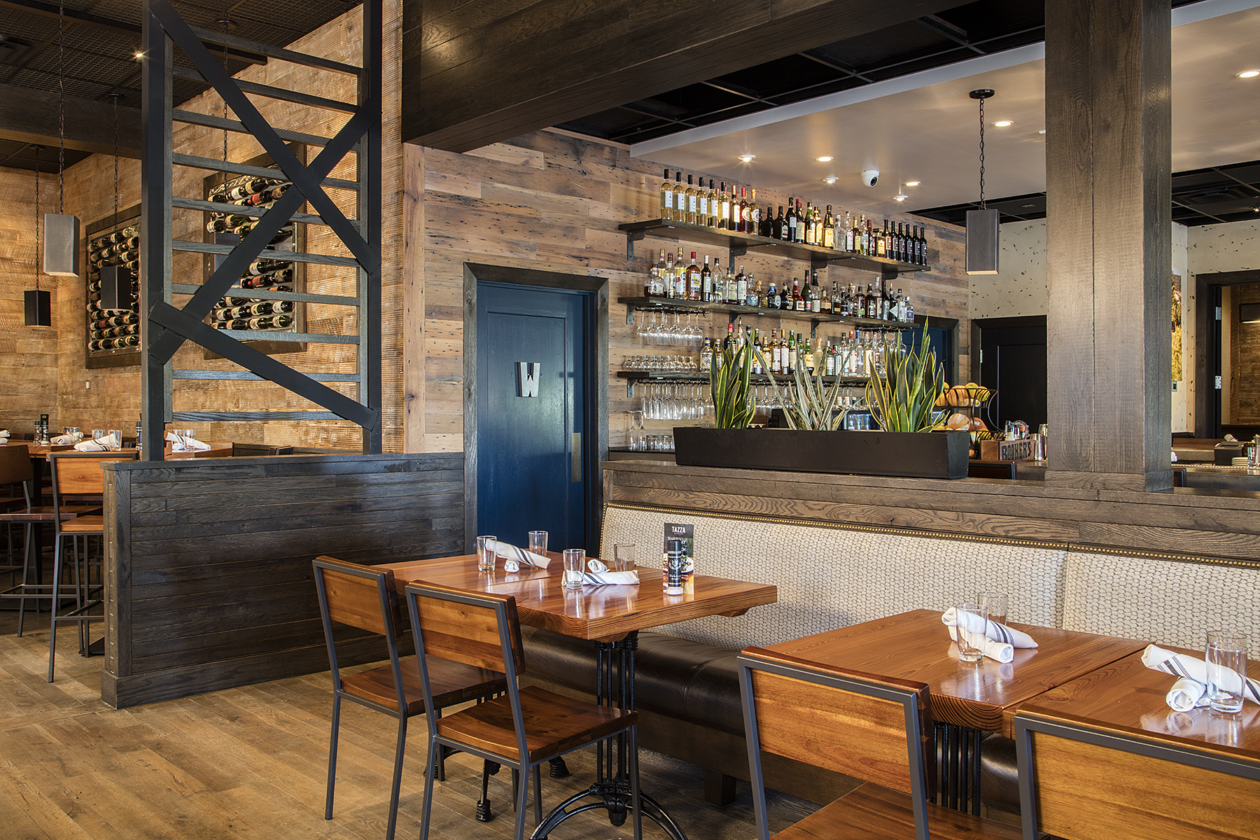 Photo: Alston Thompson Photography  Floor, wall panelling, tables, and chairs at Tazza Kitchen, Midlothian, Virginia provided by Surface Architectural Supply