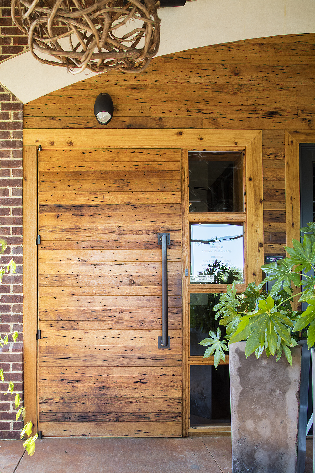 Photo: Alston Thompson Photography  Knotty pine sourced by Surface Architectural Supply marks the entrance at Tazza Kitchen in Midlothian, Virginia.