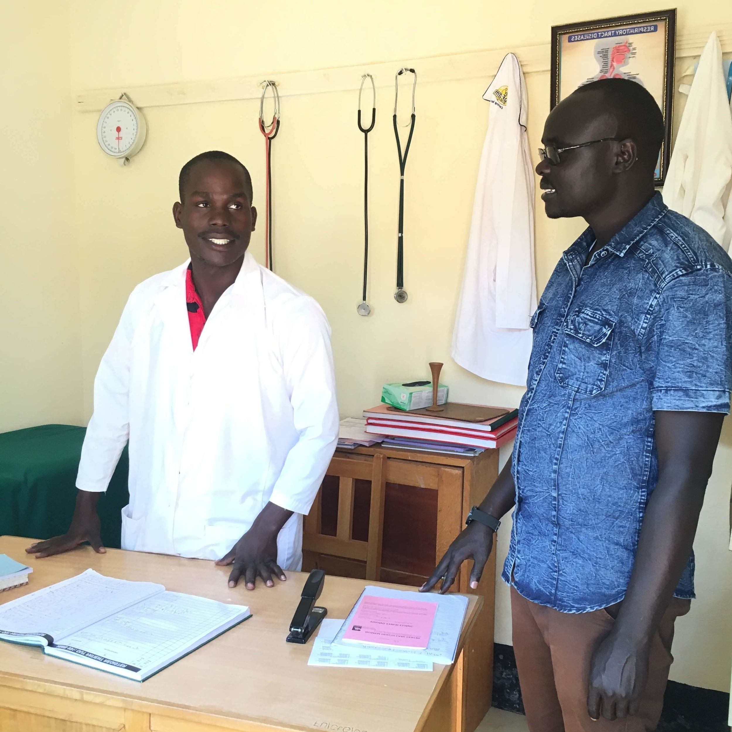 Co-founder, Oyet Patrick (right), discusses with head clinical officer, Opiyo Morish (left), about the lack of healthcare providers in Northern Uganda as one of the reasons for poor access to quality health care.