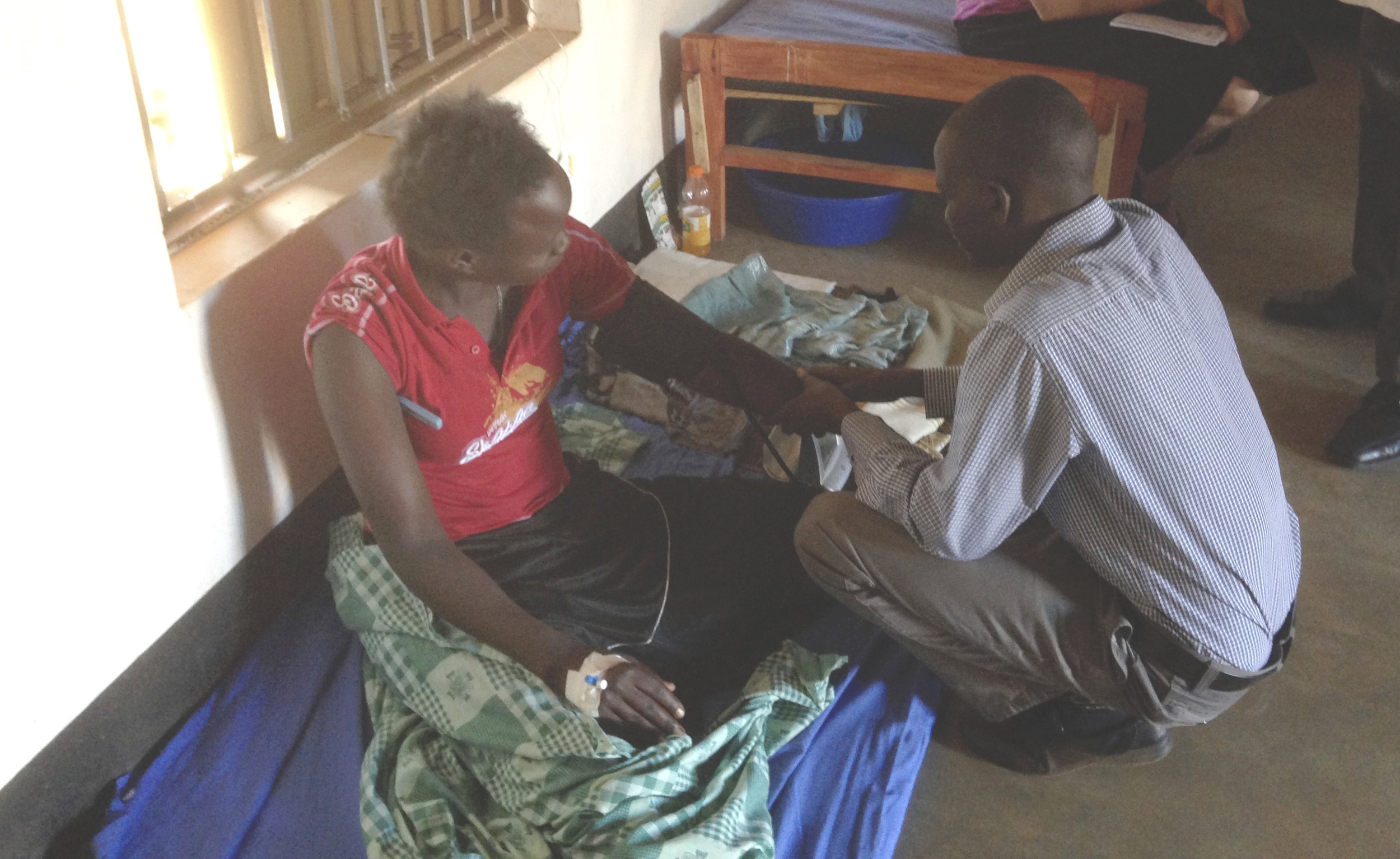 Nursing assistant, Peter, attends to a young woman awaiting morning rounds in the inpatient ward of NUMEM clinic