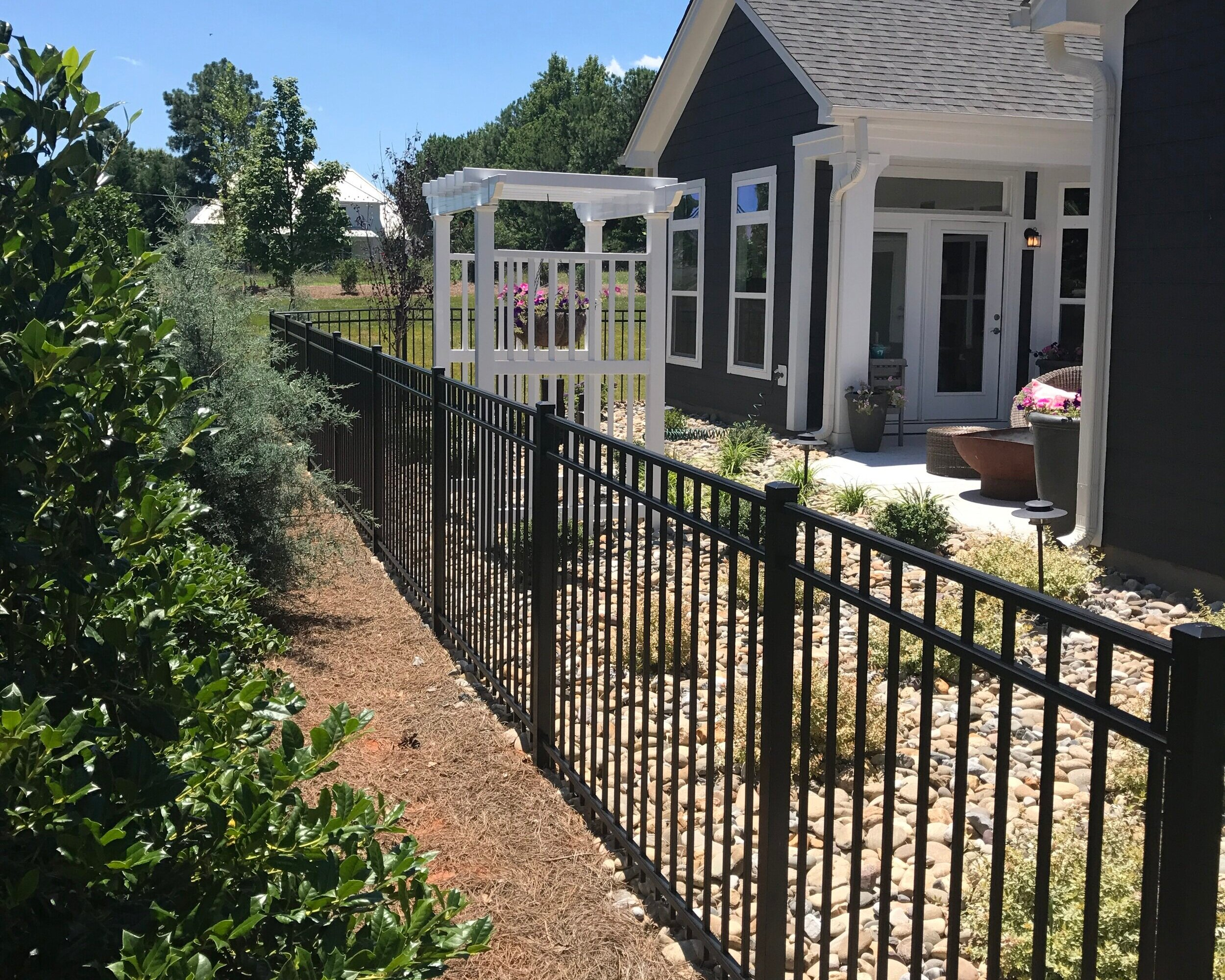 Beautiful ornamental aluminum fence manufactured by Alumi-Guard with a vinyl arbor fabricated by Gaston Fence Co., Inc. all installed by the talents professionals at Gaston Fence.