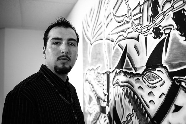 Black and white photo portrait of artist Raul Maldonado standing in front of one of his drawings