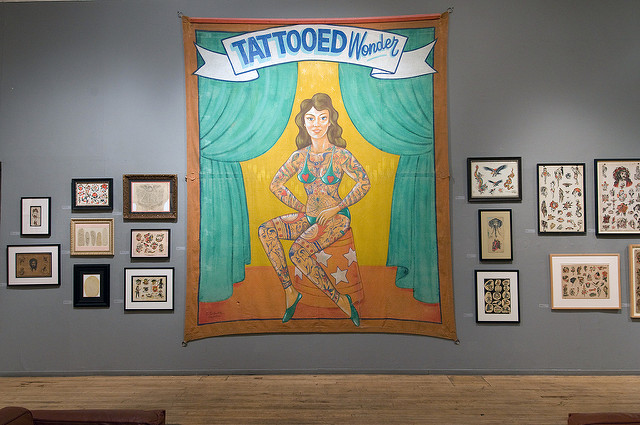 "Gallery installation view with decals and freakshow banner of tattooed woman flanked by green curtains seated under banner with text ""TATTOOED Wonder"""