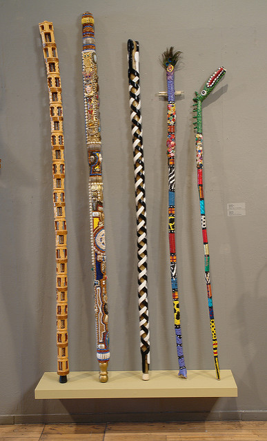Photo of gallery view with five colorful sticks installed on a shelf