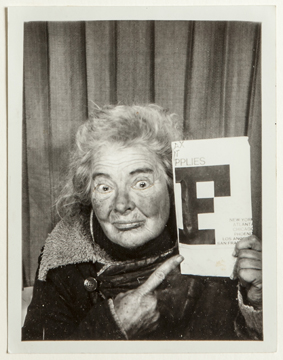 Photo booth self-portrait of Lee Godie pointing to paper she's holding