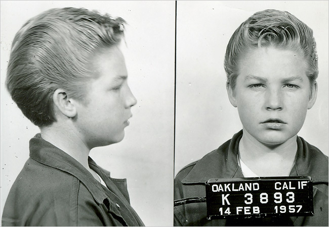 Black and white profile and head on mugshot of young boy taken in Oakland, California on February 14, 1957