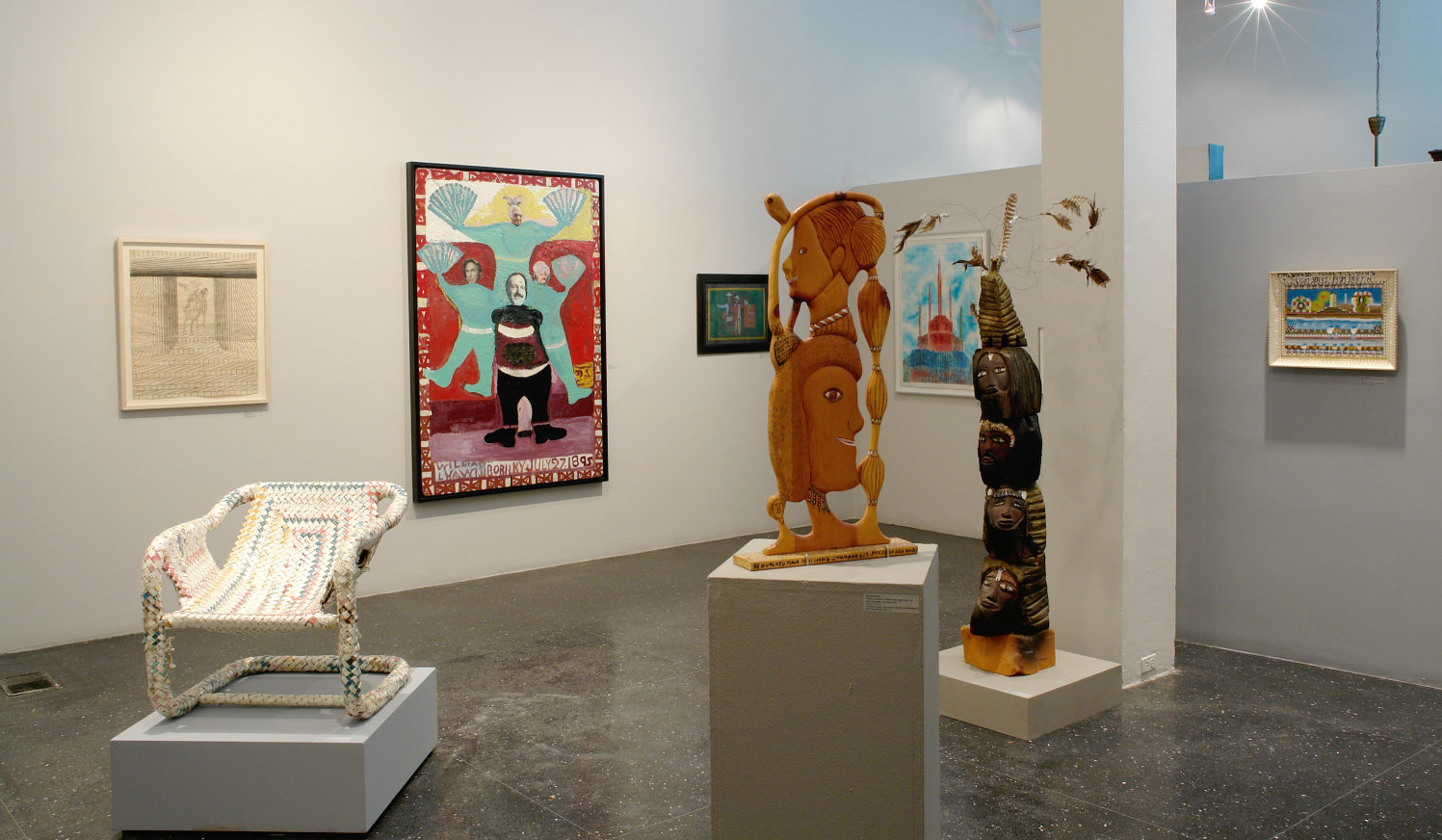 View of installation featuring sculptures in foreground and paintings and drawings on gallery walls