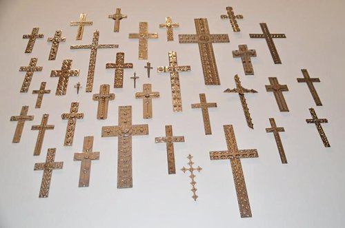 Gold and brown crosses installed on gallery wall