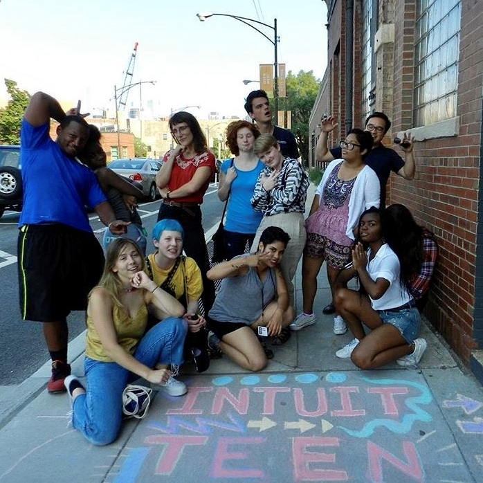 Group shot of teens with chalk sign on sidewalk