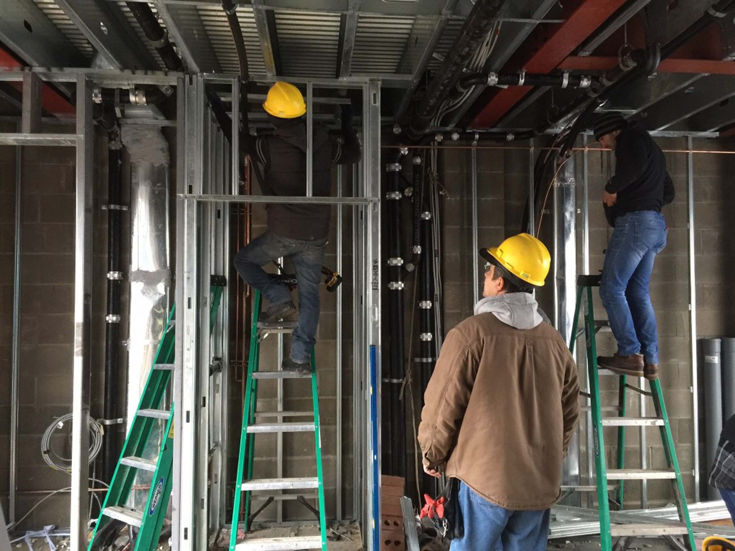 Workers outfitting the bottom of the metal decking with plumbing pipes