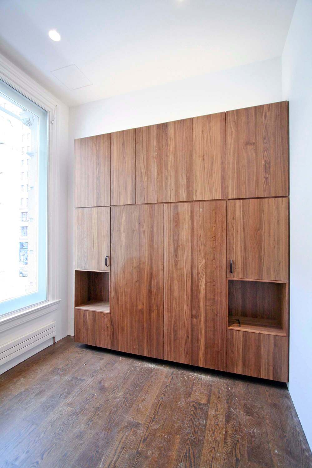 Guest Bedroom  -  Murphy Bed integrated into the Walnut millwork with side cubbies and storage above.