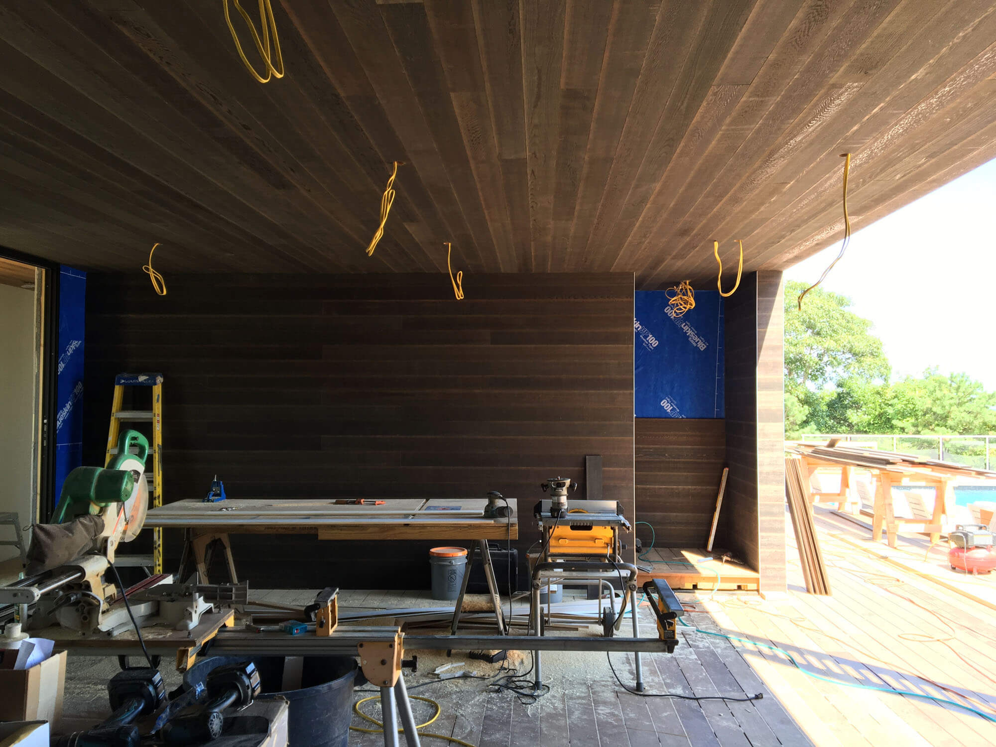 Enclosed deck space  -  A stained cedar wall separates a partially enclosed deck space from an exterior stair leading to the roof space.