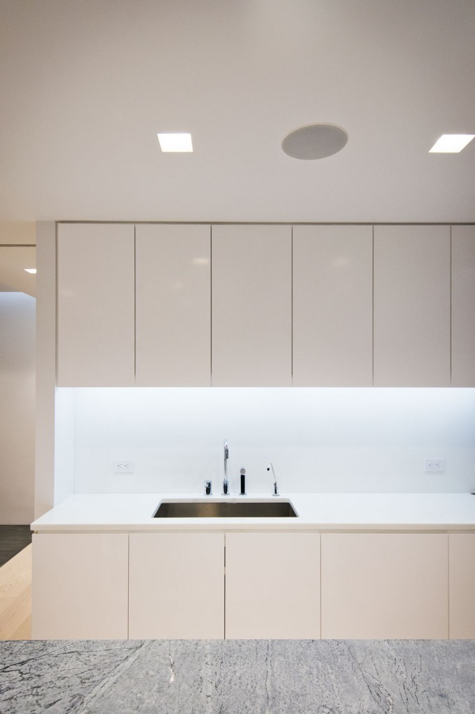 Kitchen  -  minimalist kitchen design with corian countertops and recessed accent lighting beneath kitchen millwork uppers.