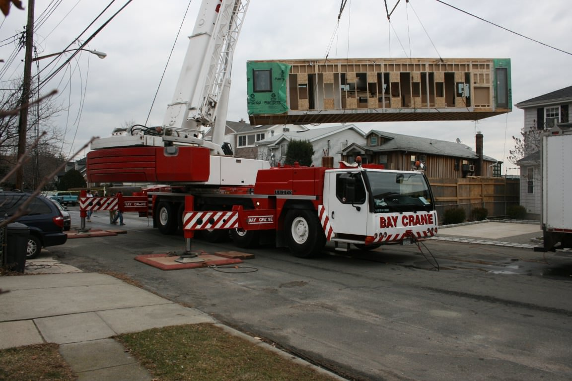 Crane lifting first prefabricated module into place.