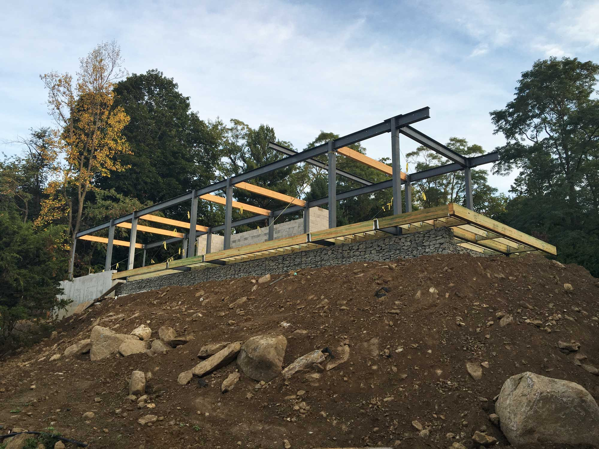 "Steel Frame & Pool Deck  --  A steel and wood pool deck cantilevers over a gabion retaining wall.  The steel columns and beams are getting ready for the ""bar"" house to be framed above."
