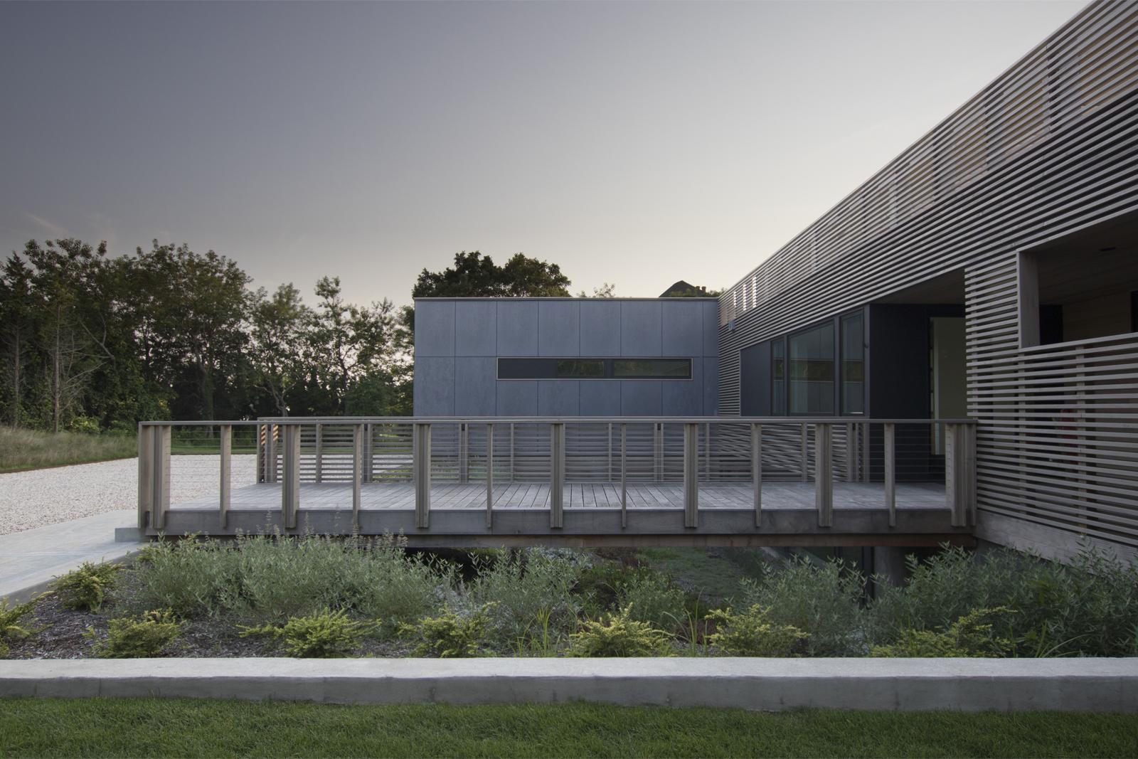 11-res4-resolution-4-architecture-modern-modular-house-prefab-home-north-fork-bluff-house-exterior-facade-elevation-bridge-entry-dusk.jpg