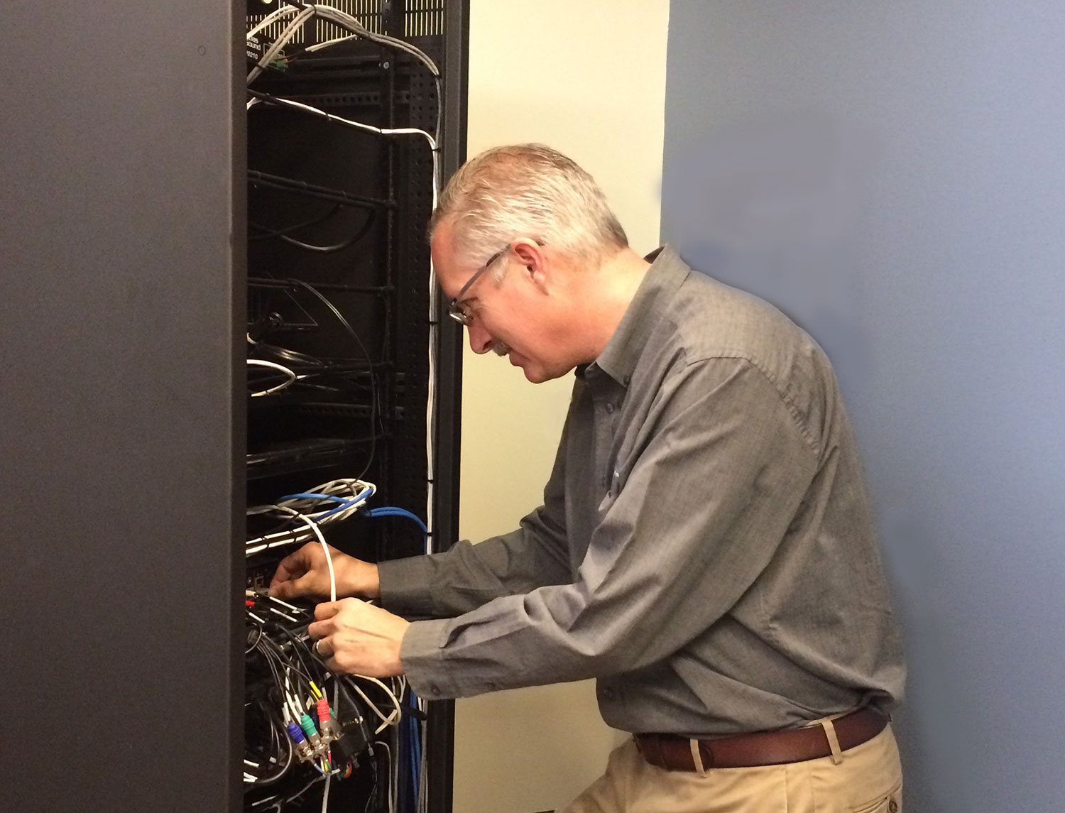 Service Technician working on an audio visual equipment rack.